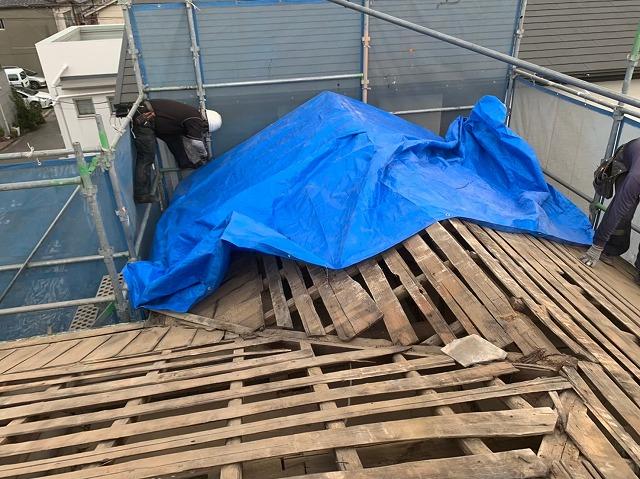 シートをかけて雨養生している写真