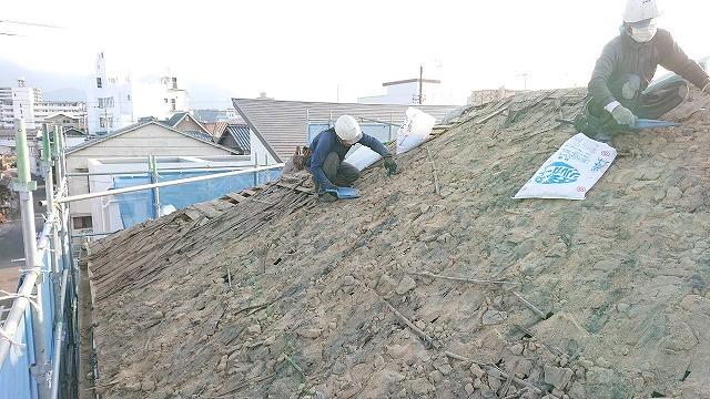屋根の葺き土の掃除している写真