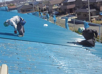 屋根カバー工法で新たな屋根を設置する作業員